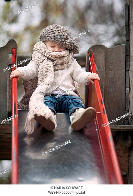 Portrait of little girl wearing big scarf and woolly hat on a slide