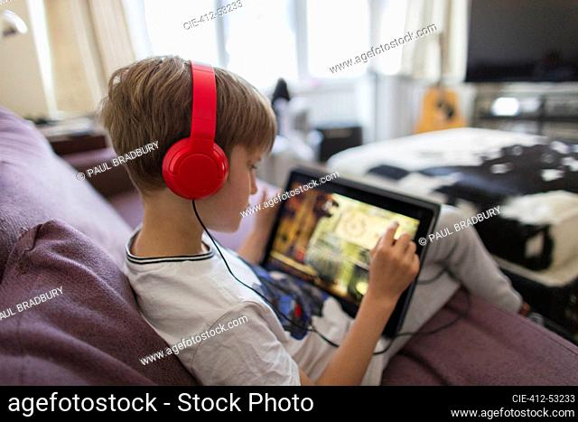 Boy with headphones and digital tablet playing video game on sofa