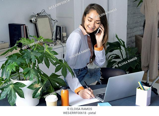 Young businesswoman working from home, talking on the phone