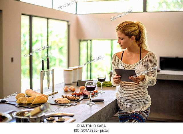 Young woman using digital whilst preparing food in kitchen