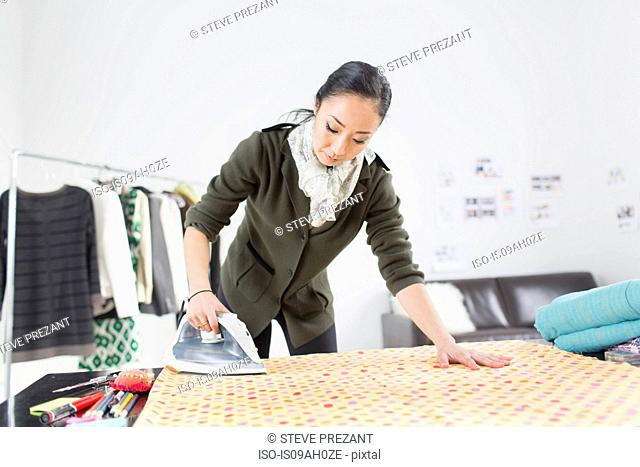 Female fashion designer ironing fabric