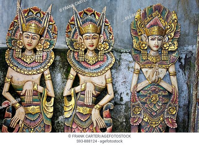 Three wooden figures of Balinese dancers in traditional dress in Ubud, Bali