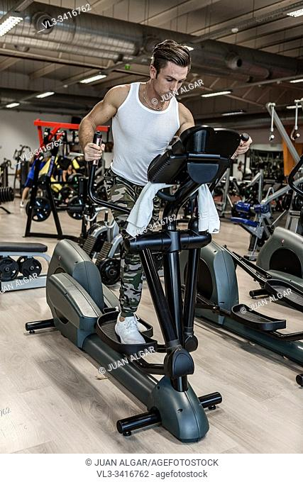 Full body determined sportswear performing exercise on modern step machine during workout in gym