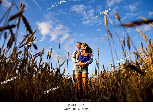 Low angle view of young couple standing on field against sky