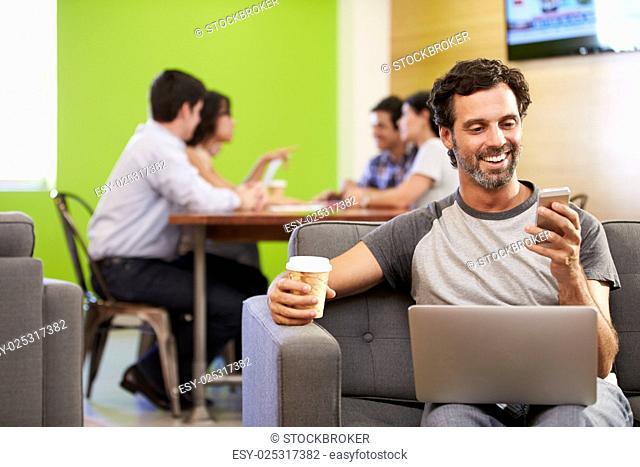 Man Sitting On Sofa And Working In Design Studio