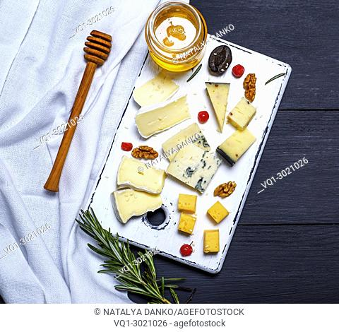 pieces of cheese on a white board and a glass jar with honey, top view