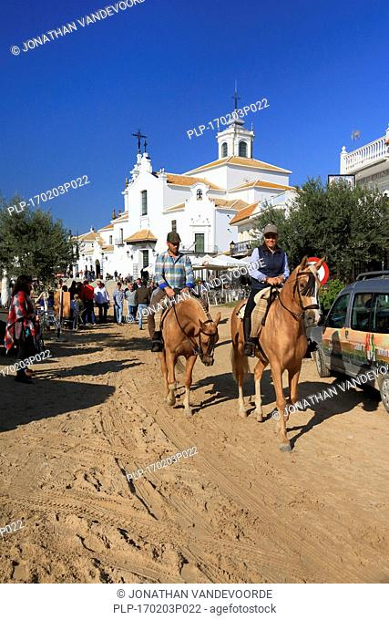 Pilgrims on horseback near the white Hermitage of El Rocío / Ermita del Rocío, Almonte, Province of Huelva, Andalucia, Spain