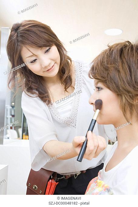 Beautician doing makeup to young woman