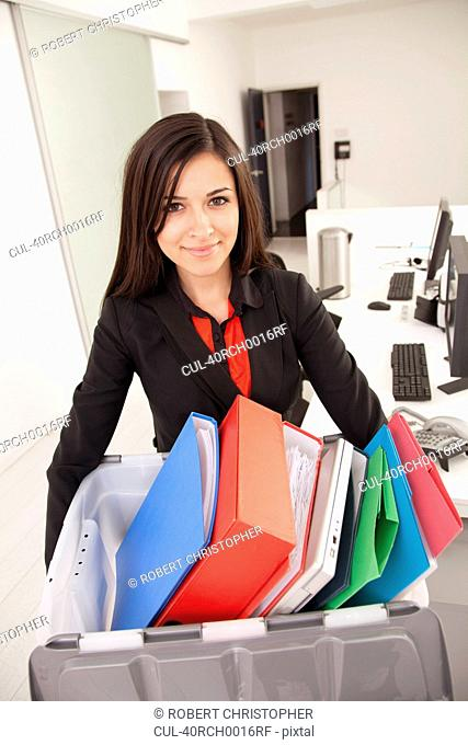 Businesswoman carrying box of binders