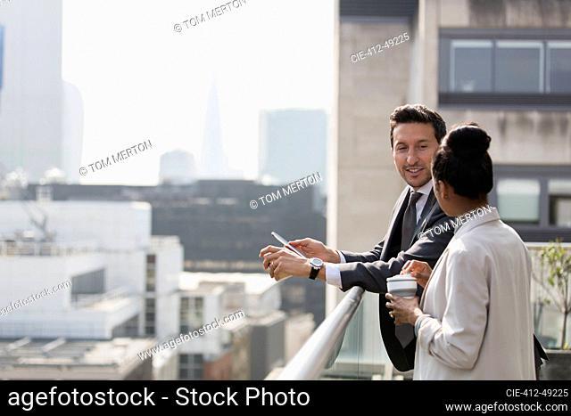 Business people talking on sunny, urban balcony