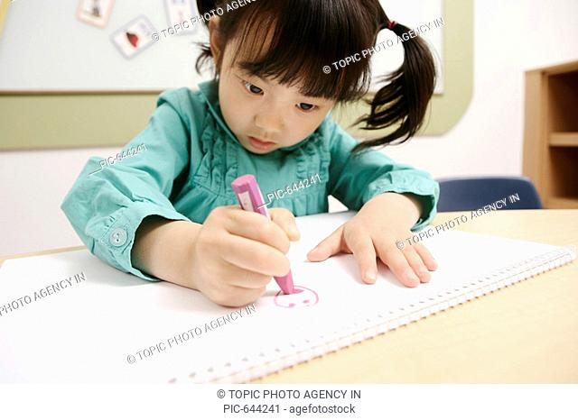 Korean Girl Drawing a Picture in the Kindergarten