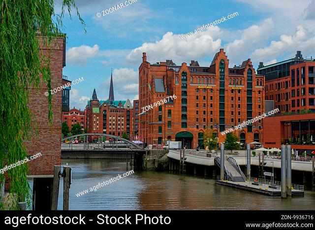 HAMBURG, GERMANY - JULY 18, 2015: a canal of Historic Speicherstadt houses and bridges at evening with amaising skyview over warehouses