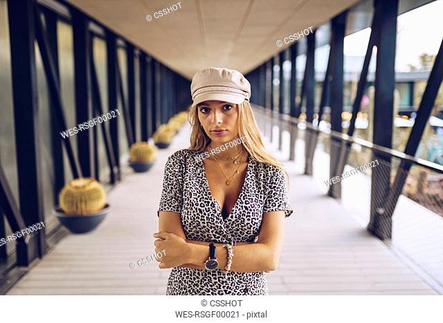 Portrait of attractive young woman standing in arcade wearing leopard print dress
