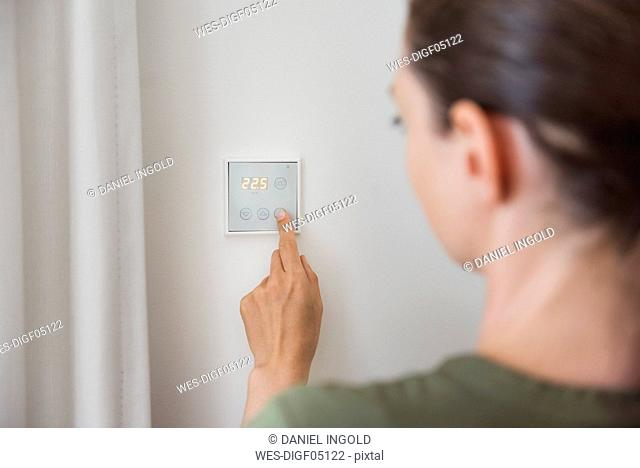 Woman using smart home switch on wall