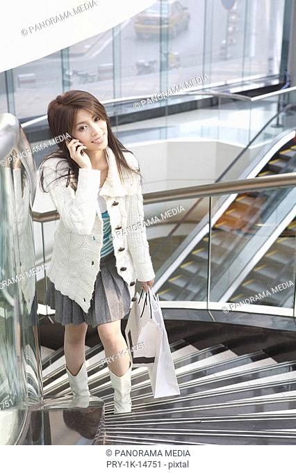 Young woman walking upstairs, holding a mobile phone