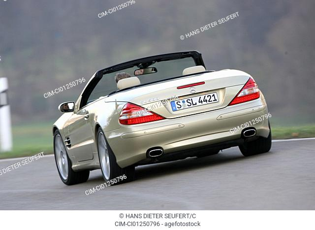 Mercedes SL 500, model year 2005-, gold, driving, diagonal from the back, rear view, country road, open top