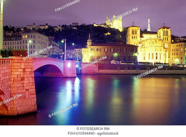 Lyon, Rhone-Alpes, France, Europe, Cathedral Saint Jean (below) and Basilique Notre Dame de Fourviere (above) illuminated at night along the Saone River in Lyon
