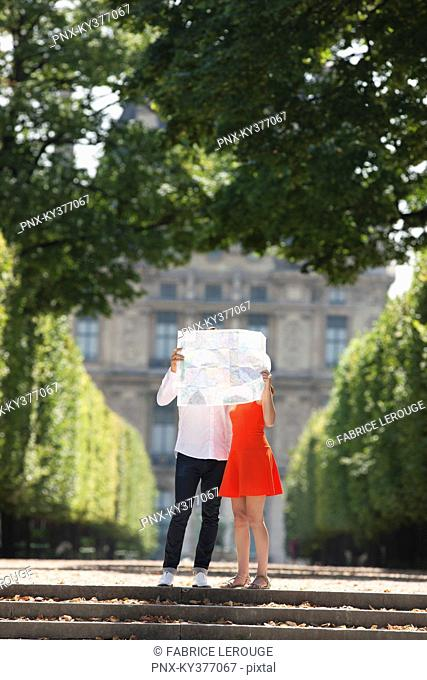 Couple holding a map in front of their faces, Terrasse De l'Orangerie, Jardin des Tuileries, Paris, Ile-de-France, France