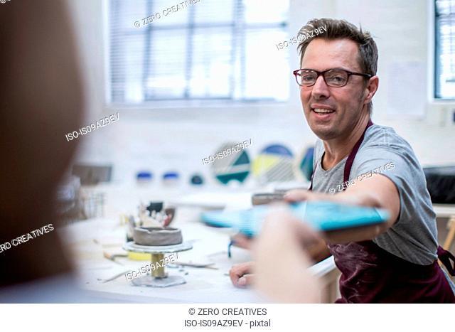 Male potter handing digital tablet in workshop