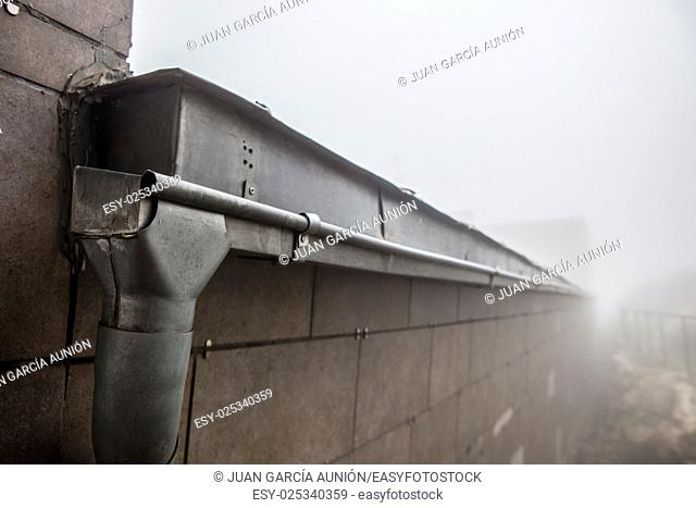 Gutter drainage system on the roof with dripping fog. Closeup