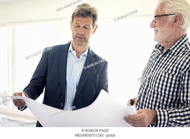 Man in suit and senior man looking at blueprint