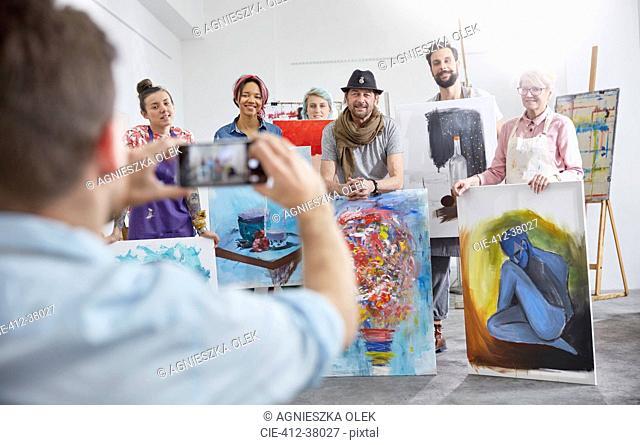 Man photographing art class classmates in art studio