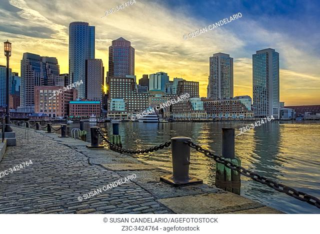 A view during sunset to the Boston Harbor with the Boston Financial District's dramatic skyline and colorful sky