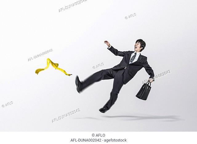 Young Japanese businessman slipping on a banana