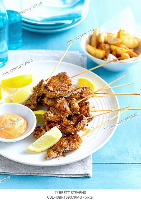 Plate of chicken skewers with sauce
