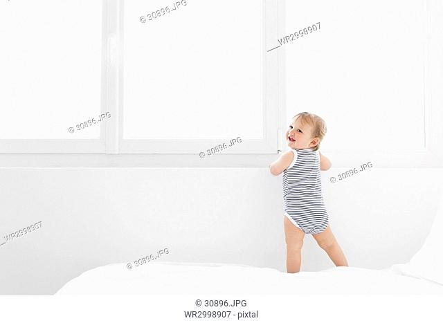 Baby boy wearing striped onesie standing on bed with white duvet