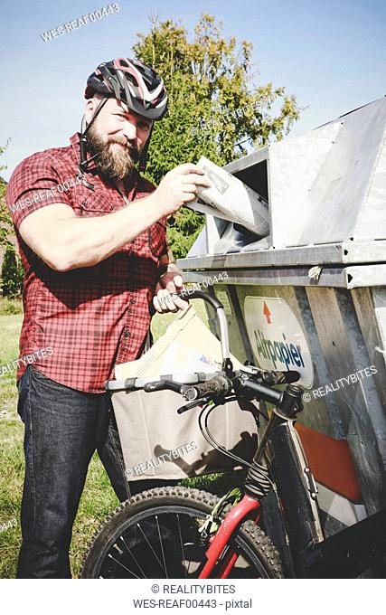 Portrait of cyclist recycling waste paper in paper bank