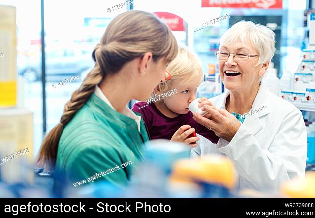 Friendly pharmacist, young mother and child having fun in pharmacy