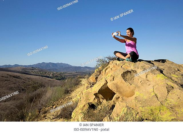 Mature woman practicing yoga on hill taking smartphone selfie, Thousand Oaks, California, USA