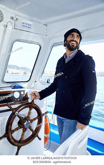Sailor, Adult man with rudder on a boat trip to Santa Clara Island, Donostia, San Sebastian, Gipuzkoa, Basque Country, Spain, Europe
