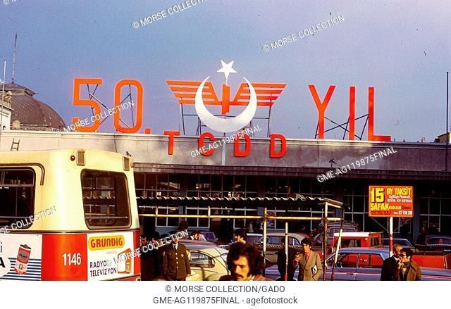 Scene outside of Sirkeci Terminal train station, in Istanbul, Turkey, November, 1973. A large sign above the entrance reads '50 YIL TCDD'