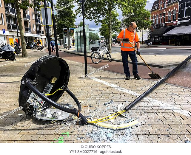 Tilburg, Netherlands. Light pole and mast being cleaned up by a city worker after it has been run over by a delivery van
