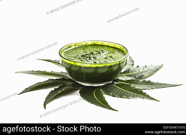 Medicinal Neem leaves with paste in bowl on white background