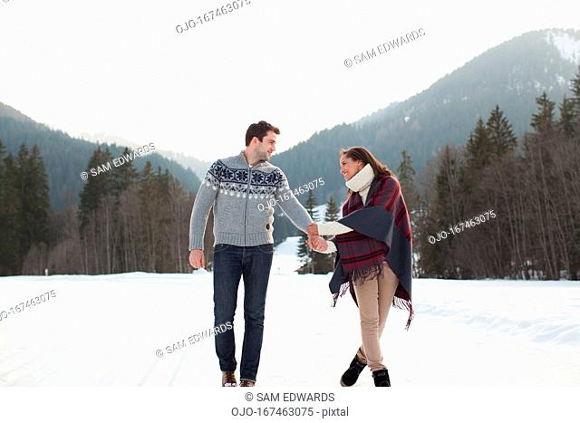 Smiling couple holding hands and walking in snowy field