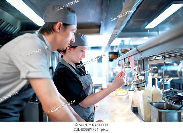 Female chef and colleague reading order in Italian restaurant kitchen