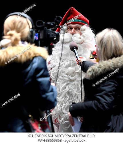 A PR person dressed up as Santa Claus answers the questions of journalists at a press event in the press area at the Nordic Ski World Championship in Lahti