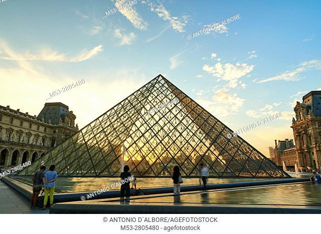 Tourists visiting the famous Louvre Pyramid. Paris. France