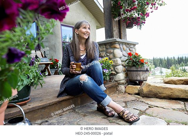 Smiling woman drinking coffee on front stoop
