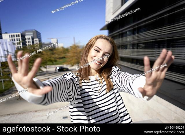Young woman making hand gesture, stop sign. Munich, Germany