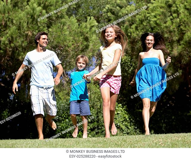 Young Family Running Through Summer Field