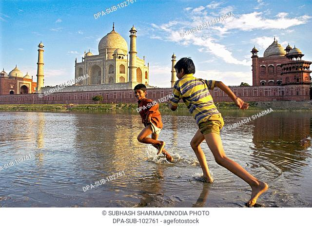 Two children playing water river Yamuna flowing Taj Mahal Agra Ancient artist artistic beautiful blue sky boys children kids clouds Color constructed 1631 A