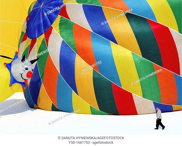 Small smiling baloon watching seriously looking man, International hot air baloons show in Chateau d'Oex, Switzerland