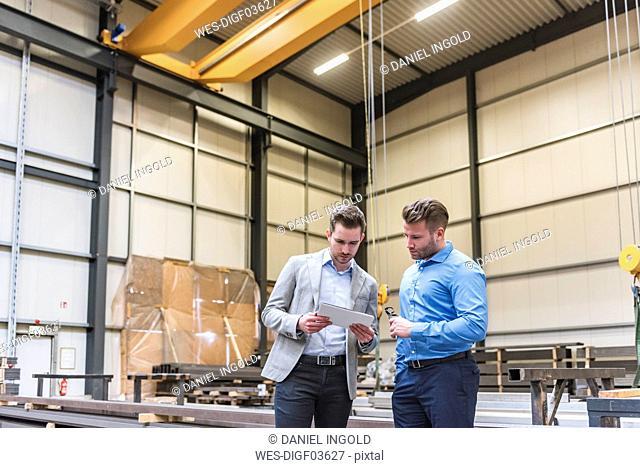 Two businessmen sharing tablet on factory shop floor