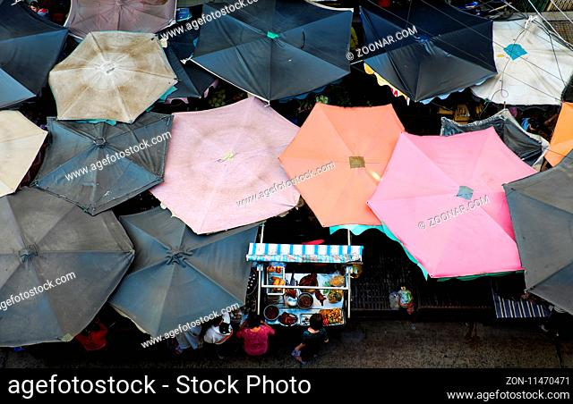 Group of sunshade from top view at outdoor farmers market, Ho Chi Minh city, Vietnam, woman at roast duck pushcart, amazing food counter from high view at...