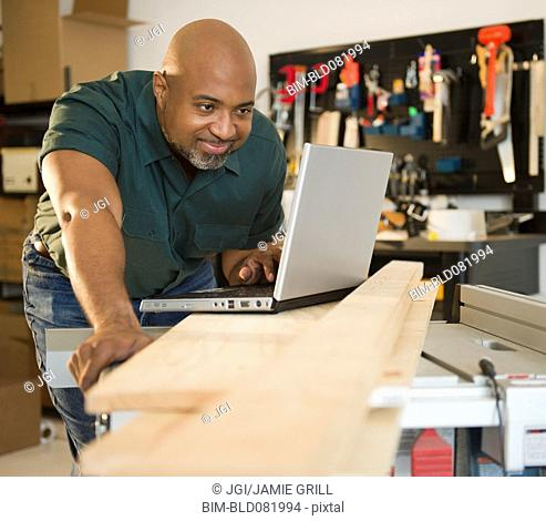 African American carpenter using laptop in workshop