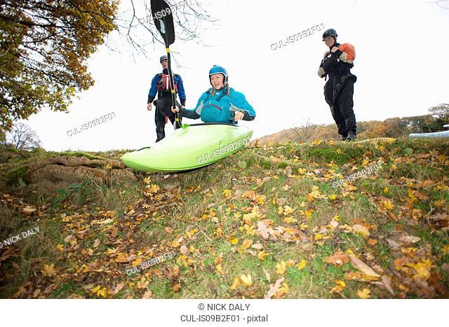 Female kayakers preparing to move down river bank in kayak